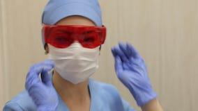 Il dentista mette sui vetri arancio protettivi prima del lavoro con il cliente video d archivio