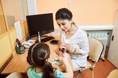 Il dentista mostra ad una bambina come pulire la protesi dentaria fotografia stock
