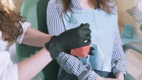 Il dentista nel suo ufficio prende il paziente, gli mostra la struttura del dente sul modello artificiale, elimina la dentina stock footage