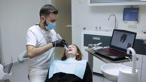 Il dentista nell'ufficio dentario comunica con il paziente e ride video d archivio
