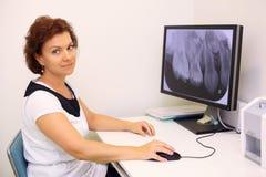 Il dentista si siede alla tabella con l'immagine dei raggi X della mascella Fotografia Stock Libera da Diritti
