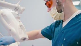 Il dentista sta lavorando nell'ufficio dentario che fa i denti che imbianca la procedura archivi video
