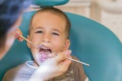 Il dentista sta trattando un boy& x27; denti di s Children& x27; odontoiatria di s, odontoiatria pediatrica Uno stomatologo femmi fotografia stock libera da diritti