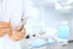 Il dentista tiene i suoi strumenti nell'ufficio fotografie stock
