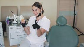 Il dentista tiene il modello sano del dente a disposizione, mostra i pollici su, gesto che buon, movimento lento video d archivio