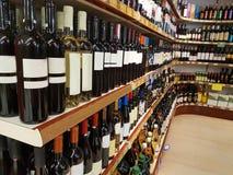 Il deposito di vino beve le bottiglie sullo scaffale Immagine Stock