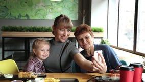 Il derivato e la nipote della nonna sono fotografati sul telefono in un caffè archivi video