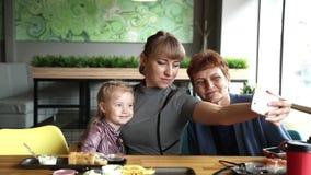 Il derivato e la nipote della nonna sono fotografati sul telefono in un caffè video d archivio