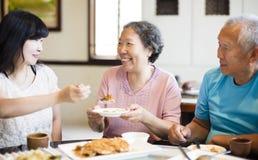Il derivato ed il genitore senior godono della cena fotografie stock