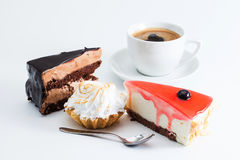 Il dessert ha messo con il caffè della tazza su fondo bianco Tre pezzi di macro rossa del bigné della torta di formaggio della mo Immagini Stock Libere da Diritti