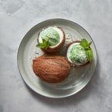 Il dessert verde di recente dolce in noce di cocco con la foglia verde della menta e noce di cocco scheggia su un piatto su un fo Immagine Stock Libera da Diritti