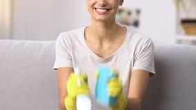 Il detersivo allegro e la pezzuola per lavare della tenuta della donna, aspettano per pulizia dell'appartamento video d archivio