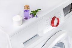 Il detersivo naturale con petrolio essenziale e lavanda fiorisce sopra la lavatrice Immagine Stock