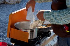 Il dettaglio del campeggiatore che versa un pacchetto dell'istante ha schiacciato le patate in un vaso di acqua bollente su una s fotografia stock libera da diritti