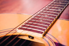 Il dettaglio della chitarra acustica mette insieme l'avvoltoio su un fondo leggero fotografia stock