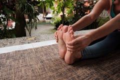 Il dettaglio della donna caucasica che fa il asana di yoga si esercita La ragazza fa la posa di andata di seduta della curvatura  Fotografia Stock Libera da Diritti