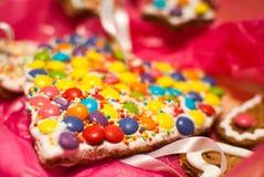 Il dettaglio di forma M&M del cuore di festa di Natale gradisce i biscotti fotografia stock libera da diritti