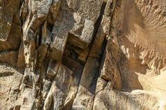 Il dettaglio sugli strati di pietra incrinati, alcuni di loro ha coperto di lichene immagini stock