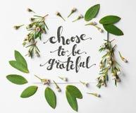 Il ` di citazione sceglie di essere ` riconoscente scritto su carta con le foglie ed i fiori su fondo bianco Vista superiore immagine stock
