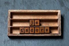Il ` di Je t adora Amo vi adoro nella traduzione francese La scatola d'annata, cubi di legno esprime scritto con le lettere di ve Immagine Stock