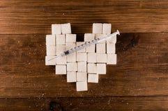 Il diabete è malattia terribile Cuore dei cubi dello zucchero con la siringa Fotografia Stock