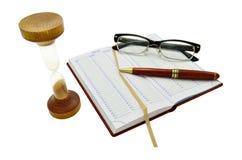 Il diario, la penna, i vetri e la sabbia cronometrano Immagine Stock