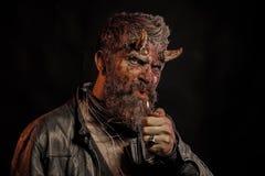 Il diavolo dell'uomo di Halloween spegne il fuoco su fondo nero immagine stock libera da diritti