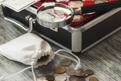 Il ` differente s del collettore conia con una borsa dei soldi e della lente d'ingrandimento Immagini Stock