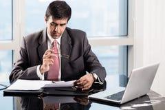 Il dirigente anziano nell'ufficio del grattacielo, leggente si contrae Immagini Stock