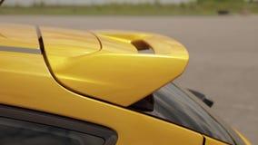 Il diruttore mette in mostra l'automobile giallo arancione nel parcheggio, gomme di basso profilo vettura da corsa di resistenza, archivi video