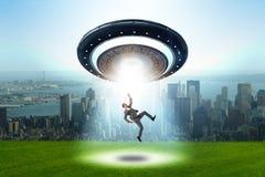 Il disco volante che rapisce giovane uomo d'affari fotografia stock libera da diritti