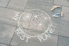 Il disegno dei bambini con i pastelli colorati su asfalto - pianeta Terra con di fiori e del di testo colorati multi - il mio mig fotografia stock libera da diritti