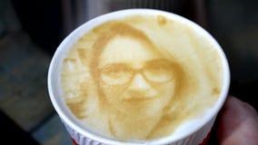 Il disegno del fronte di una donna su un latte del caffè della schiuma ha creato di da una stampante 3D archivi video