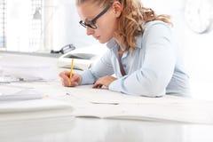 Il disegno dell'architetto blueprints, allo scrittorio in ufficio, con la matita Immagini Stock Libere da Diritti