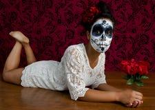 Il dispiacere del cranio dello zucchero mette sul pavimento che tiene i suoi fiori Fotografia Stock Libera da Diritti