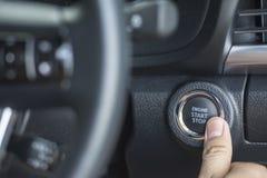 Il dito che preme il tasto di arresto di inizio del motore di un'automobile Fotografie Stock Libere da Diritti