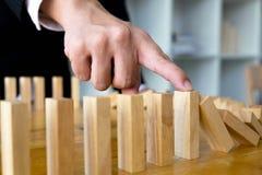 Il dito di affari ferma il significato capovolto continuo di domino che ha ostacolato il fallimento Faccia tappa questo concetto  fotografie stock libere da diritti