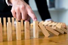 Il dito di affari ferma il significato capovolto continuo di domino che ha ostacolato il fallimento Faccia tappa questo concetto  immagini stock libere da diritti