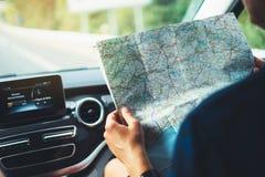 Il dito di sguardo e del punto dell'uomo dei pantaloni a vita bassa sulla mappa di navigazione di posizione in automobile, nell'a immagine stock libera da diritti