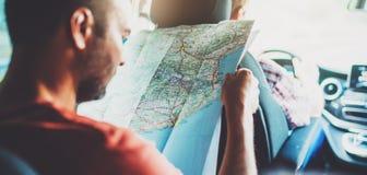 Il dito di sguardo e del punto dell'uomo dei pantaloni a vita bassa sulla mappa di navigazione di posizione in automobile, nell'a fotografia stock