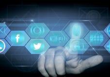 Il dito di una persona clicca sopra un ologramma con i segni delle reti sociali fotografie stock