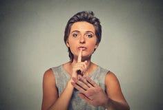 Il dito serio della donna di ribaltamento, mano sulle labbra, shhh chiedere di gesto è silenzio calmo Fotografia Stock Libera da Diritti
