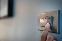 Il dito sta accendendo un interruttore della luce Immagine Stock