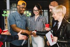 Il diverso caffè bevente di conversazione multirazziale dei giovani facendo uso dei dispositivi in ufficio accogliente, lavorator immagini stock libere da diritti
