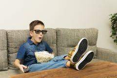 Il divertimento ha eccitato il ragazzo in vetri 3D che guarda la TV con controllo di remo e del popcorn nel salone Fotografia Stock
