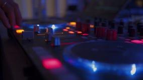 Il DJ alla discoteca sta lavorando dietro il telecomando Pista da ballo e musica leggera Il DJ nel night-club video d archivio