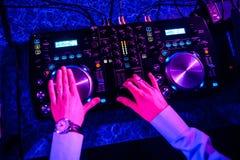 Il DJ che determina musica su attrezzatura professionale in night-club Fotografia Stock Libera da Diritti