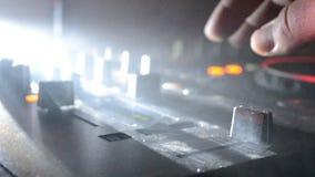 Il DJ che fila, mescolantesi e graffiante in night-club, mani comandi della pista del ritocco del DJ di vari sulla piattaforma de archivi video