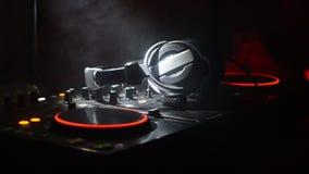 Il DJ che fila, mescolantesi e graffiante in night-club, mani comandi della pista del ritocco del DJ di vari sulla piattaforma de stock footage