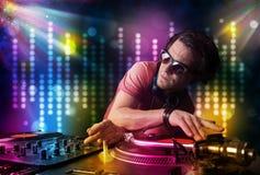 Il DJ che gioca le canzoni in una discoteca con lo spettacolo di luci Immagine Stock